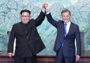 """North Korea's leader Kim Jong Un (L) and South Korea's President Moon Jae-in (R) raise their jointed hands during a signing ceremony near the end of their historic summit at the truce village of Panmunjom on April 27, 2018. The leaders of South and North Korea embraced warmly after signing a statement in which they declared """"there will be no more war on the Korean Peninsula"""". / AFP PHOTO / Korea Summit Press Pool / Korea Summit Press Pool"""